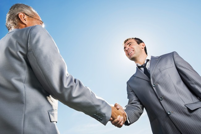 Businesspeople shaking hands against the sky.